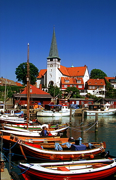 Boats in the harbor of Roenne in front of the Nicolaichurch, Bornholm, Denmark
