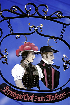 Wrought-iron sign at an inn, couple wearing traditional Black Forest costumes, Baden-Wuerttemberg, Germany, Europe
