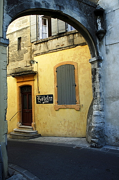 Entrance with sign to abandoned two star hotel viewed from beneath an old stone arch in a narrow street in Arles, France