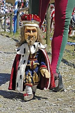 Puppet player in mediaeval medieval costume holding little marionette king , knight festival Kaltenberger Ritterspiele, Kaltenberg, Upper Bavaria, Germany