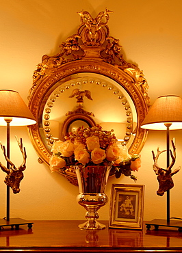 Artificial flowers in a vase placed in front of a gold-framed mirror