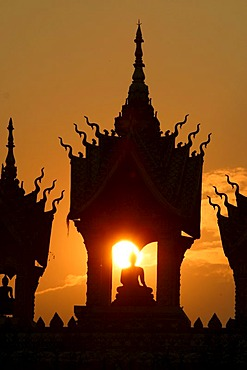 Sunset behind a Buddha statue at That Luang Vientiane, Laos, Asia