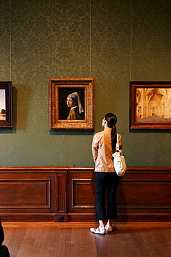 "Girl watching the famous painting ""Girl with a Pearl Earring "" by Dutch painter Johannes Vermeer in the museum Mauritshuis in The Hague Netherlands"