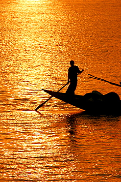 Boatman silhouetted in the evening sun, Hooghly River, Kolkata (Calcutta), West Bengal, India, South Asia
