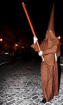 Penitent dressed in brown penitential robe (nazareno) carrying large candle at night, Semana Santa, Holy Week Procession, Huelva, Andalusia, Spain