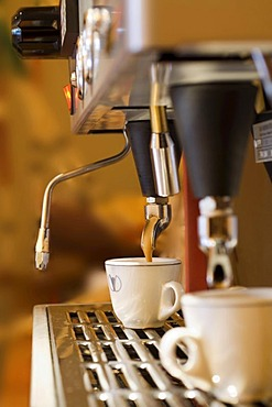 A cup of coffee is prepared with an espresso machine