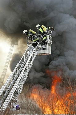 German fire brigade men fights a blaze in a warehouse in Munich Bavaria Germany.