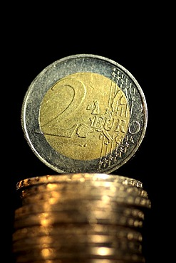 Two Euro coin is standing up to a pile of Euro coins