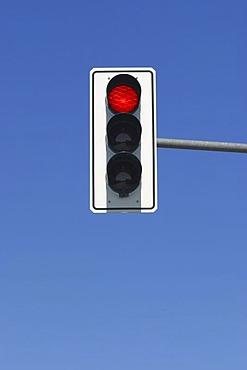 Red traffic light in blue sky