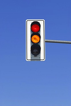 Red and yellow traffic light in blue sky