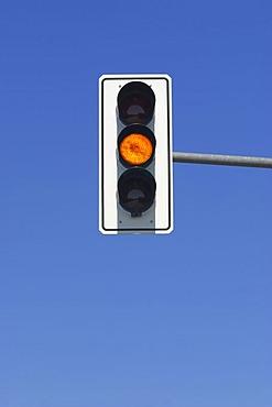 Yellow traffic light in blue sky