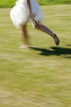 Young woman runs in a white dress without shoes over a meadow