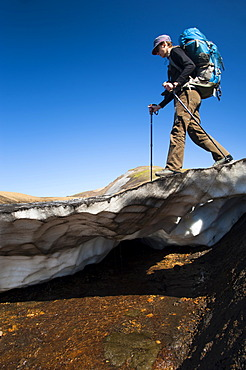 Female hiker walking on a snow slab, on the Laugavegur hiking trail, Hrafntinnusker-Álftavatn, Fjallabak Nature Reserve, Highlands of Iceland, Iceland, Europe
