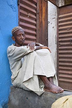 Dealer sitting outside his shop, at a street market, Bo, Southern Province, Sierra Leone