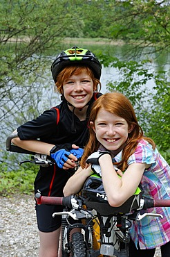 Two children, boy and girl, with mountain bikes and helmets