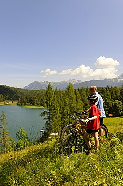 Cycling tour with mountain bikes, father and son in front of Lake Lautersee, Mittenwald, Karwendel Mountains, Werdenfelser Land, Upper Bavaria, Bavaria, Germany, Europe