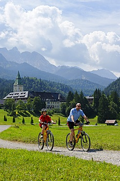 Cycling tour with mountain bikes, father and son in front of Schloss Elmau Castle, Mittenwald, Wetterstein Range, Werdenfelser Land, Upper Bavaria, Bavaria, Germany, Europe