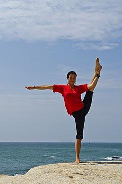 Woman in a yoga position, Anjaneyasana, by the sea in Kanyakumari, Tamil Nadu, India, Asia