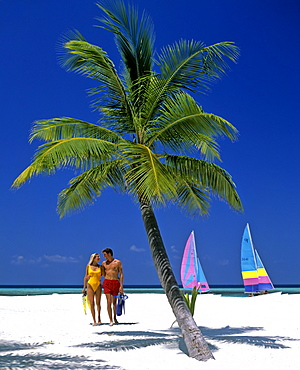 Palm tree, young couple on the beach with snorkeling gear, catamarans, Maldives, Indian Ocean