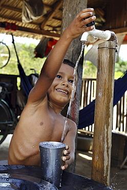 Boy filling water into a drinking vessel, Amazon Basin, Brazil