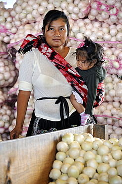 Indigene woman carrying a small girl in a sling, standing in front of bags of onions, CENMA, vegetable wholesale market in the south of Guatemala City, Guatemala, Central America