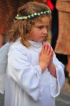 Little blond girl dressed as an angel in white with wings, flower garland and hands clasped in prayer during the Semana Santa, Holy Week festivities in La Nucia, Costa Blanca, Spain