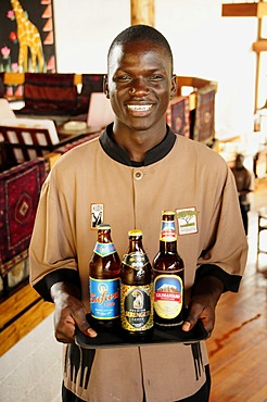 Waiter carrying the three most popular beers in Tanzania, Serengeti, Kilimanjaro and Safari, Lobo Wildlife Lodge, Serengeti National Park, Tanzania, Africa
