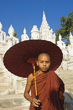 Young Buddhist monk with a red umbrella, Settawya Pagoda, Mingun, Burma, Myanmar, South East Asia