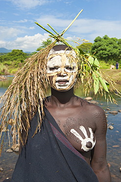 Young Surma woman with body painting in front of the river, Kibish, Omo valley Valley, Ethiopia, Africa
