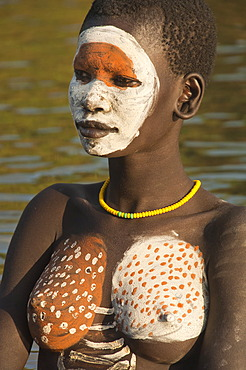 Young Surma woman with body painting in the river, Kibish, Omo valley Valley, Ethiopia, Africa