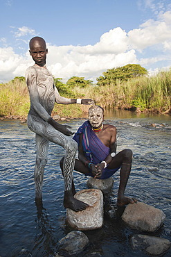 Two Surma men with facial and body paintings in the river, Kibish, Omo River Valley, Ethiopia, Africa