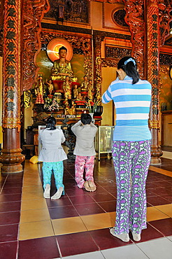 Women in prayer in a Buddhist temple, Vietnam, Asia