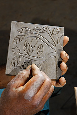 Ornament being carved into a decorative plate, manufacture of pottery, Bamessing, Cameroon, Africa