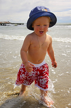 Little boy on the beach running through the water, Caorle, Veneto, Italy