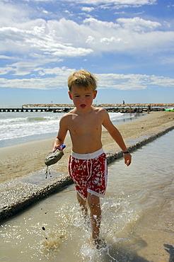 Boy with shovel on the beach, Caorle, Veneto, Italy