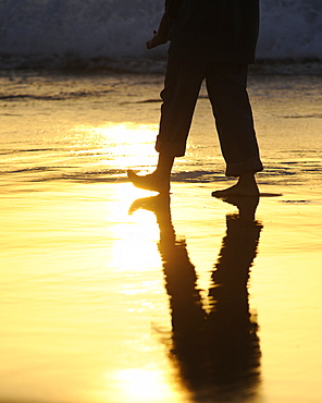 Legs walking along a beach, backlighting, near El Cotillo, Fuerteventura, Canary islands, Spain, Europe