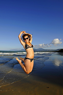 Young woman by the sea jumping in the air, symbolic of lust for life, Four Mile Beach, Port Douglas, Daintree National Park, Queensland, Australia
