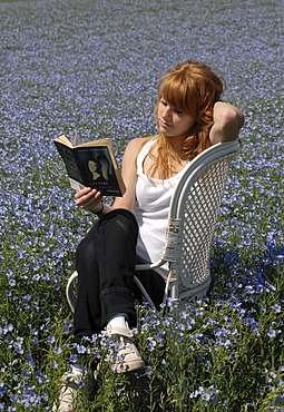 Reading girl sitting in a chair in a field of linen