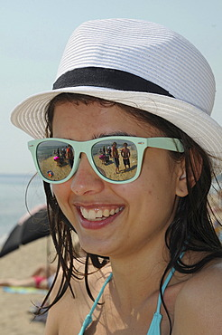 Smiling girl on the beach, wearing sunglasses