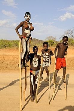 Boys of Ari tribe walking on stilts, Omo Valley, Ethiopia, Africa