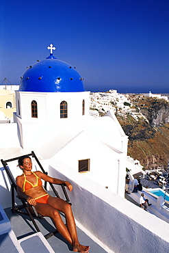 Woman lying on a deckchair on the terrace of a hotel near Thira, Santorini, Cyclades, Greece, Europe