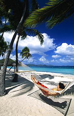 Woman in a hammock under palm trees on a beach on Peter Island, British Virgin Islands, Caribbean