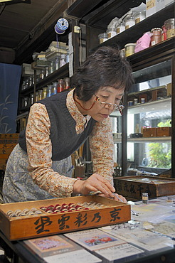 Sales clerk showing different mineral colours for Nihonga painting in a traditional shop for art supplies, Kyoto, Japan, Asia