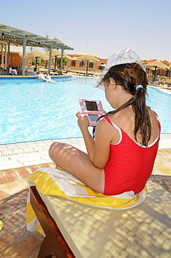 Girl, eight years, on holiday, playing with a Game Boy, a Nintendo DS at the pool