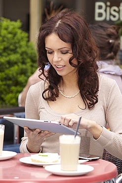 Young woman using an iPad tablet computer in a sidewalk cafe