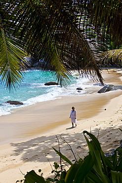 Woman walking along the beach wearing a tunic, Mahé Island, Seychelles, Indian Ocean, Africa
