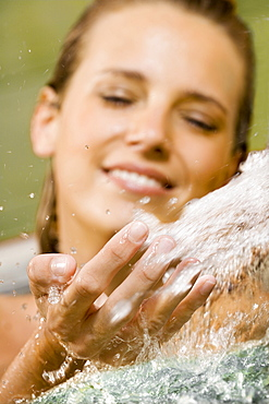 Woman relaxing in a hot bath, letting fresh water flow over her hand