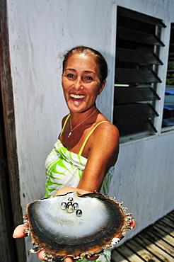 Woman with pearls, Tauahei pearl farm, Raiatea or Ra'iatea, Leeward Islands, Society Islands, French Polynesia, Pacific Ocean