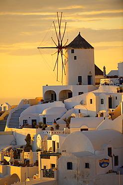 Windmills and town at sunset, Oia, Ia, Santorini, Cyclades Islands, Greece, Europe