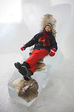 Tourist on an armchair made of ice, sitting on reindeer fur against the cold, Jukkasjaervi, Lappland, Northern Sweden